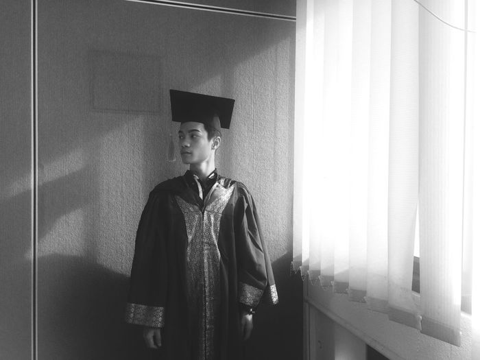 Young Man In Graduation Gown Standing At Home