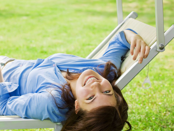Portrait Of Happy Young Woman Lying On Seat At Park