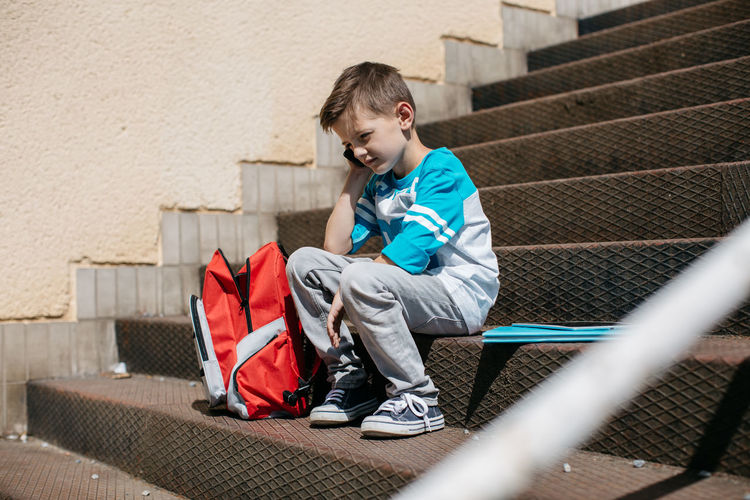 Full length of boy sitting on steps with backpack during sunny day