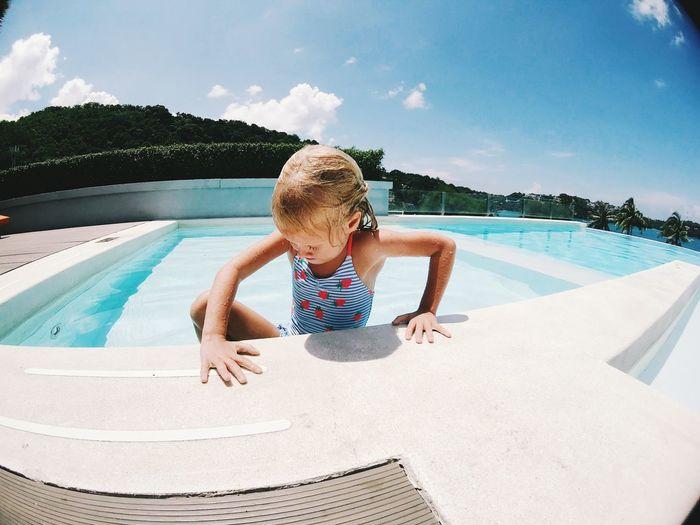 Cute girl in swimming pool against sky