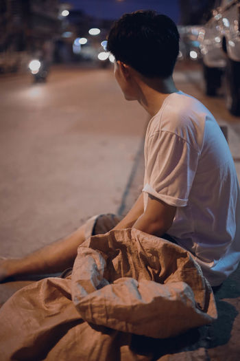 Thoughtful homeless man sitting on roadside in city