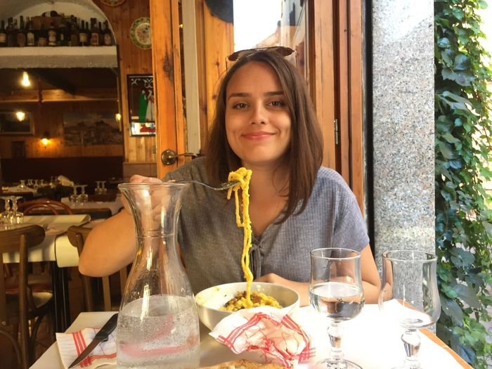 Portrait Of Smiling Young Woman Having Noodles At Restaurant Table