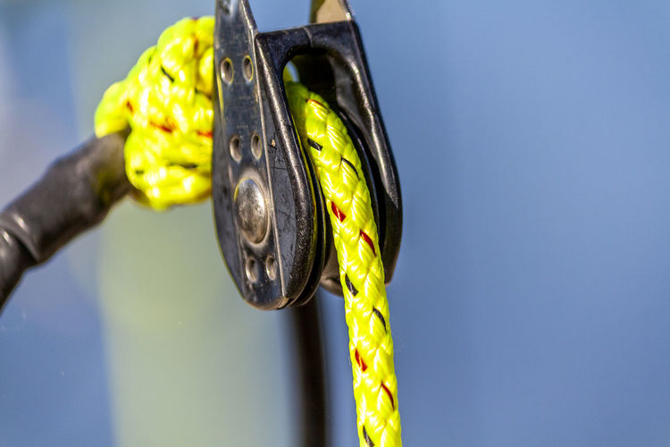Close-up of rope hanging on metal against blue background