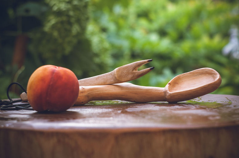 Close-Up Of Wooden Spoon And Carving Fork By Peach On Wet Wood