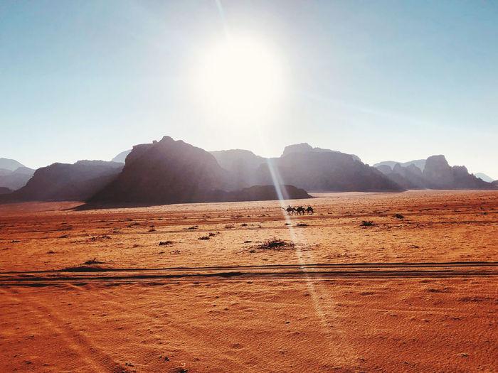 Scenic view of desert against sky on sunny day