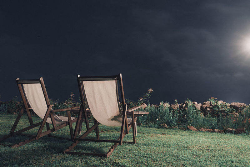 Chairs on field against sky