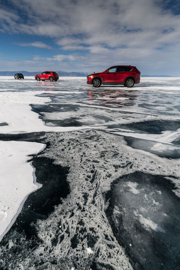 Red car on snow covered land against sky