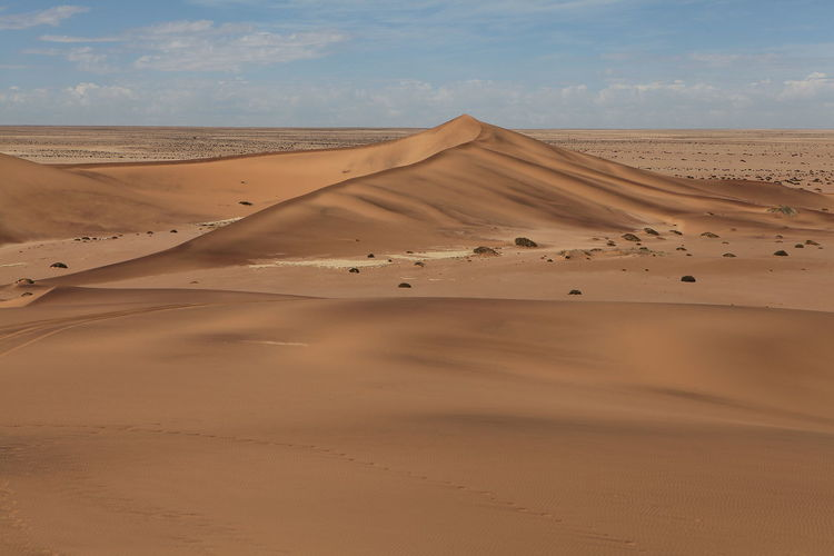 Scenic View Of Sand Dunes In Desert Against Cloudy Sky