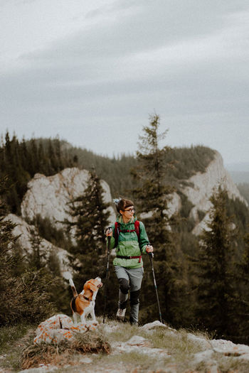 Woman with dog on mountain against sky