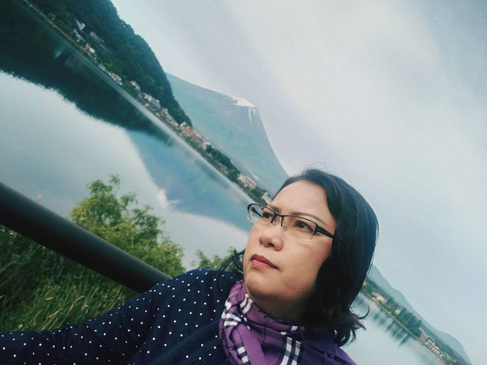 Tilt Image Of Thoughtful Mature Woman Looking Away While Standing By Lake Against Sky