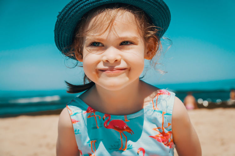 Summer Child Girl Kid Sea Beach Water Sky Childhood Portrait Land Front View Hat One Person Innocence Leisure Activity Looking At Camera Real People Cute Girls Women Smiling Lifestyles Focus On Foreground Outdoors