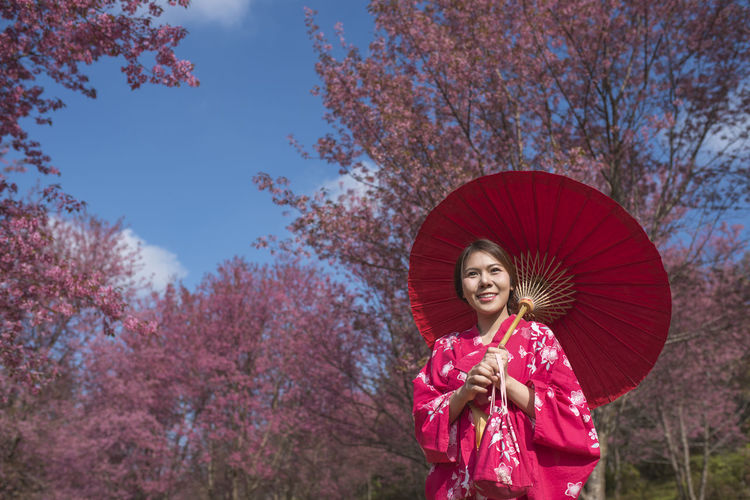 Smiling woman with umbrella standing against trees