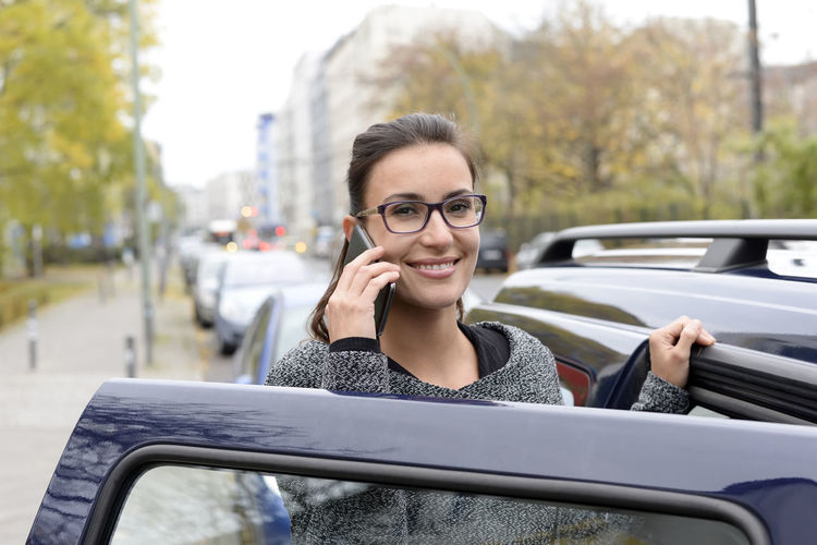 Portrait Of Smiling Young Woman Talking On Mobile Phone By Car In City
