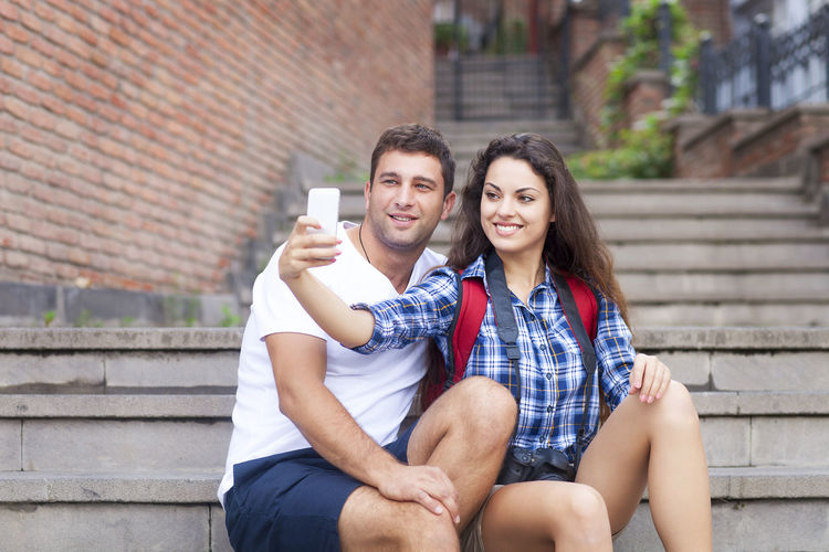 Portrait of young couple sitting outdoors