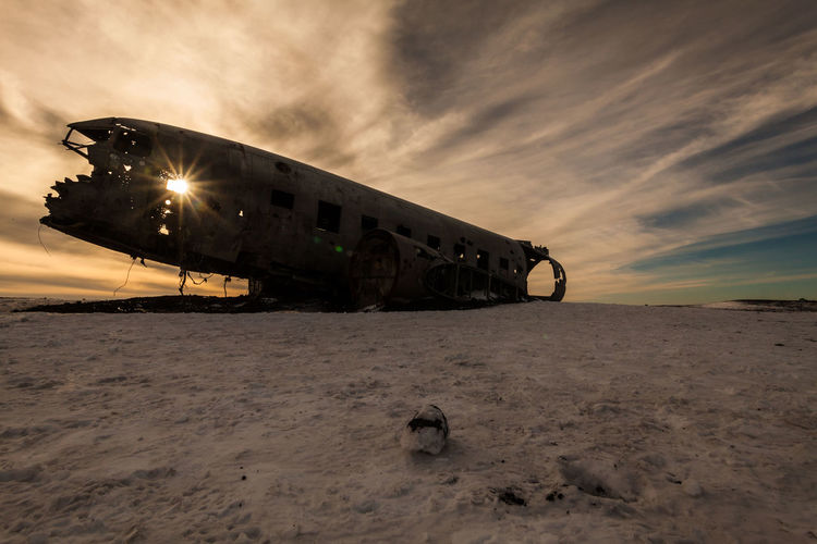 Abandoned airplane on sand at beach against sky during sunset