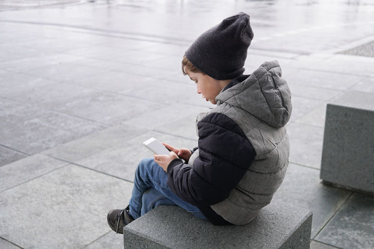 7 year old boy with smartphone Digital Native Winter Boy Cell Child Childhood Holding Kid Lifestyles Mobile One Person Outdoors Phone Playing Real People Smart Phone Smartphone Street Technology Warm Clothing Wireless Technology