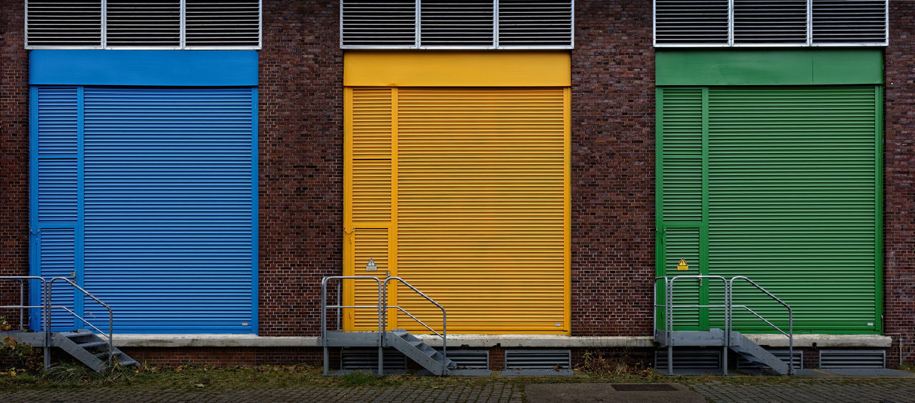 Rolling gates. Bremen 2017 Blue, Yellow And Green Rolling Gates. Bremen 2017 Bremen Germany GERMANY🇩🇪DEUTSCHERLAND@ Rolltore Blau, Gelb Und Grün Bremen Deutschland Corrugated Iron Industry Multi Colored Shutter