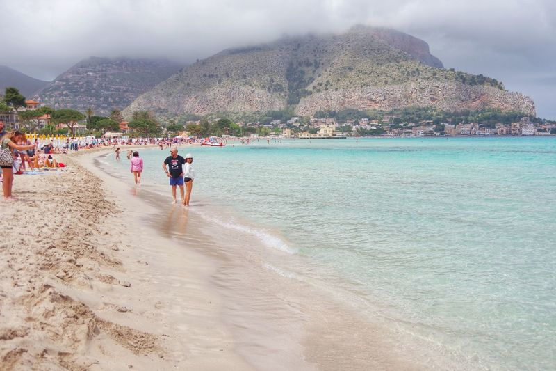 Mondello (Sicily), Italy. April 30, 2018. Mondello is a small seaside resort with a wonderful beach just a short bus ride from the centre of the Sicilian capital Palermo. Palermo, Sicily - Mondello beach. Mondello is more or less a suburb of the city, and excursions to the sea at Mondello are a ritual for Palermitani. Palermo Sicilia Beach Beauty In Nature Day Group Of People Holiday Land Lifestyles Men Mondello Mountain Nature Outdoors Real People Sand Scenics - Nature Sea Sky Trip Vacations Water Women