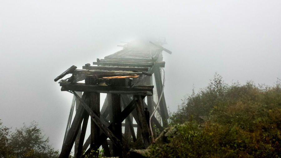 Old Railroad Track To Nowhere . Between Skagway Alaska and the Yukon Territory Canada along the White Pass. Broken and Dark Truss . Fogged in Abandon Wooden Track Fog Canadian USA Border Traveling Photography Traveling In Alaska Travel #leisure
