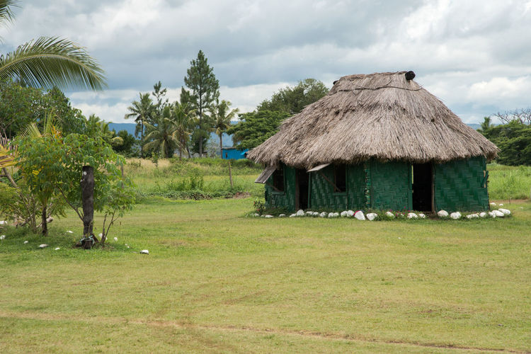 Nadi, Fiji - November 27th, 2016: Thatched roof village hut with greenery and storm cloud in the tropical climate of Nadi, Fiji Travel Animal Themes Architecture Beauty In Nature Built Structure Day Field Fiji Grass Growth Hut Landscape Nadi Nature Outdoors Pacific Islands Remote Scenics Sky Storm Cloud Stormy Thatched Roof Tranquility Tree Village
