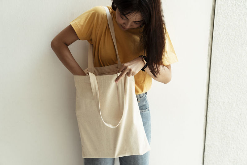 Woman checking bag while standing by wall