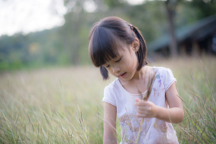 Girl holding reed while standing amidst plant