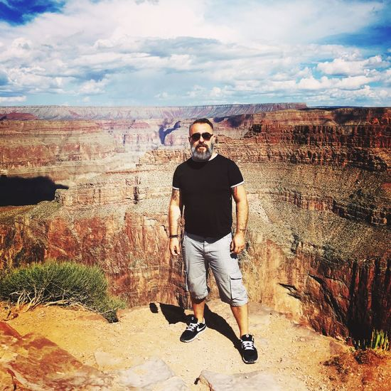 Grand Canyon Real People Sunglasses One Person Young Men Young Adult Rock Formation Front View Leisure Activity Full Length Casual Clothing Outdoors Rock - Object Sky Day Lifestyles Landscape Looking At Camera Standing Cloud - Sky Nature
