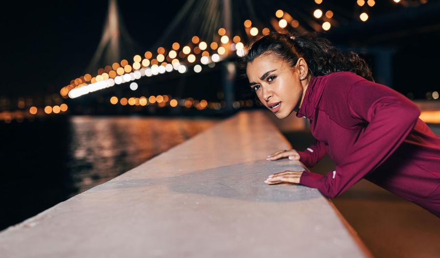 Portrait of smiling woman sitting on illuminated bridge at night