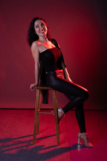 Full length of woman sitting on chair against wall