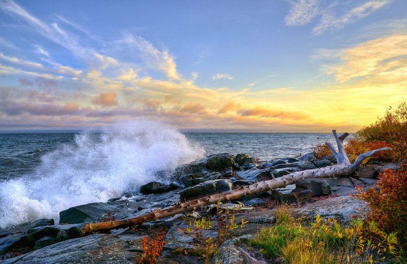 Waves breaking on rocks against the sky