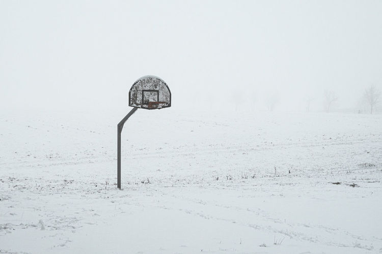 Street light on snow covered field against sky
