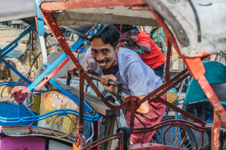 Portrait Of Smiling Man Standing Amidst Pedicab