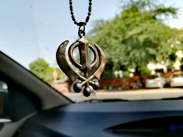 Close-up of khanda hanging in car