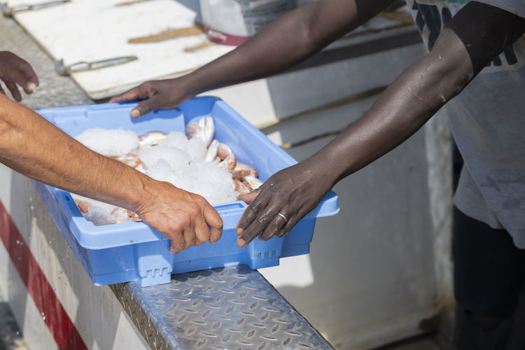 Midsection of man holding fish in container at market