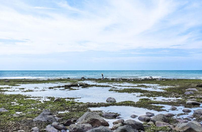 Man walking beside seaside