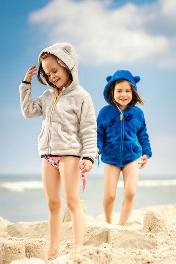 Siblings standing at beach