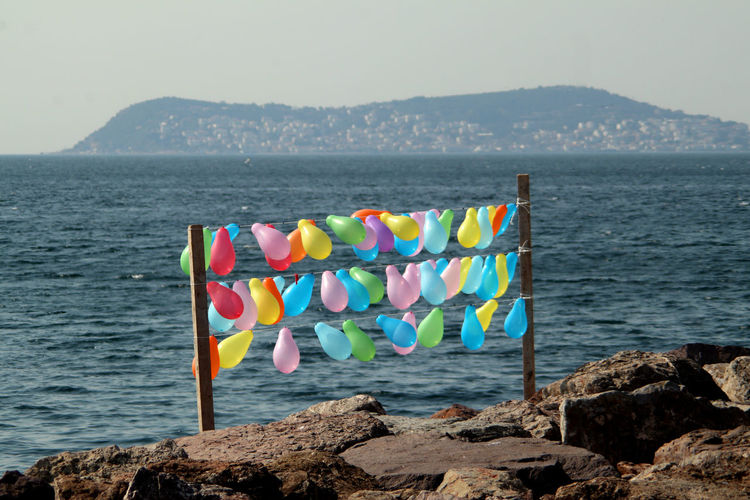 Multi colored umbrellas on rock by sea against sky