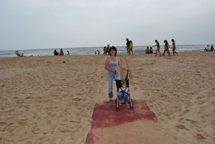 Mother Standing With Son At Sandy Beach