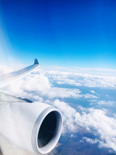 Airplane flying over clouds against blue sky