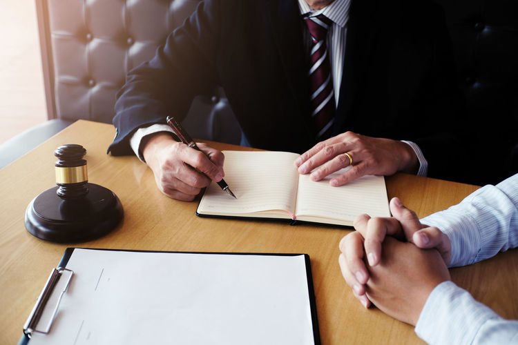 Cropped image of judge writing in book while nervous client sitting at desk