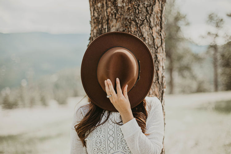 Woman standing next to a tree and holding a brown fedora next to her face