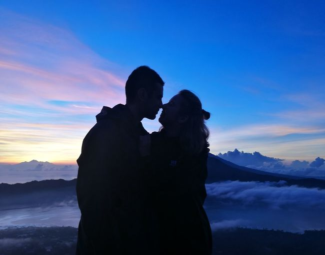 Silhouette Couple Standing On Mountain Against Sky During Sunset