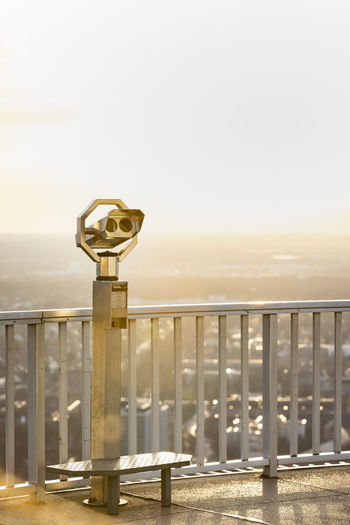 Coin-operated binoculars by railing against clear sky