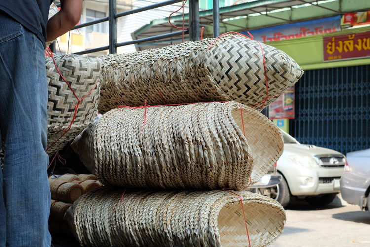 Midsection Of Vendor Standing By Wicker Basket Bundles At Market Stall