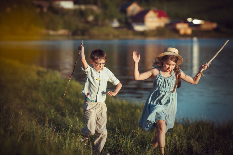 Girl and boy holding stick running by lake