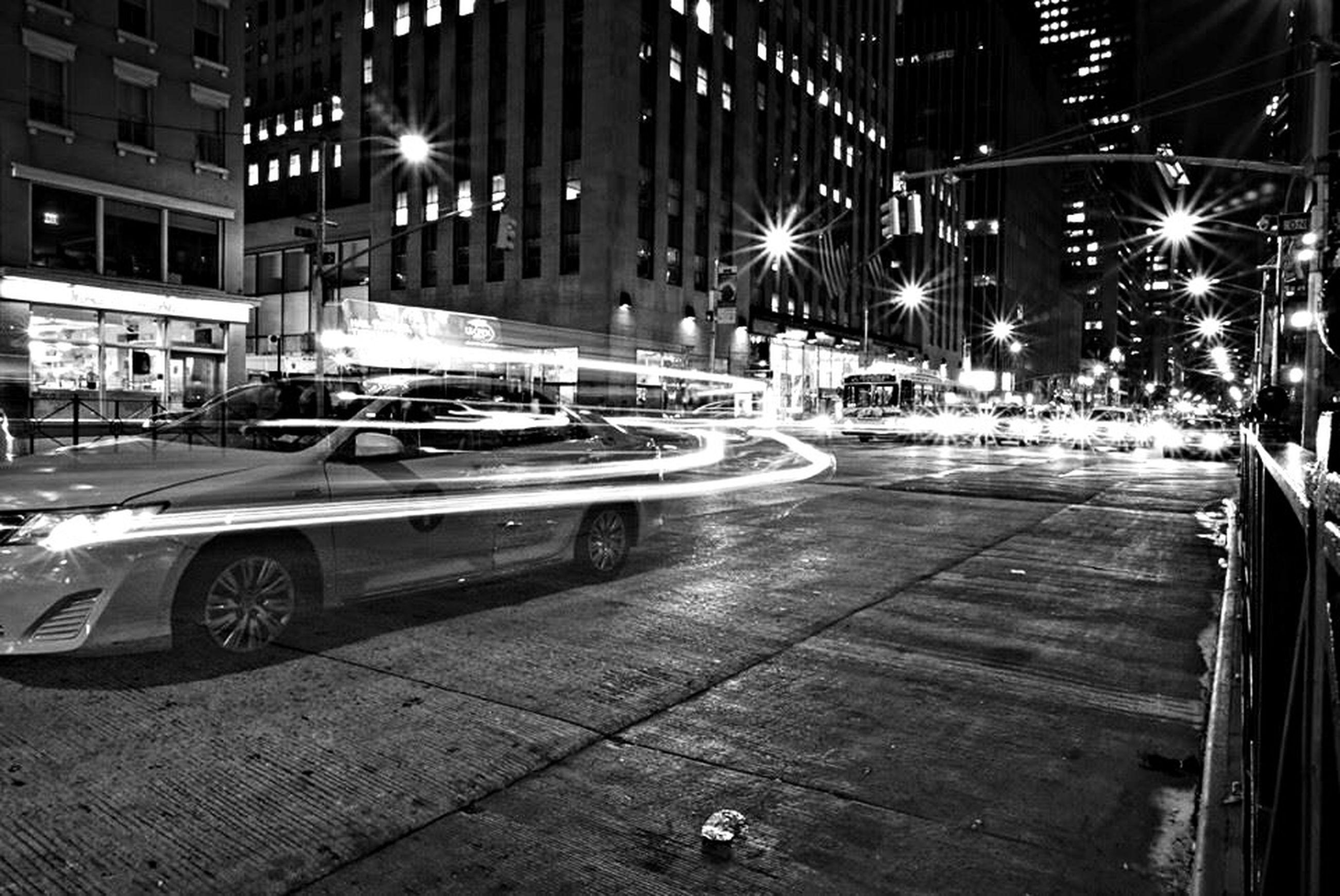 night, illuminated, transportation, street, land vehicle, building exterior, mode of transport, car, city, street light, architecture, built structure, city street, road, lighting equipment, sidewalk, city life, outdoors, incidental people, motion