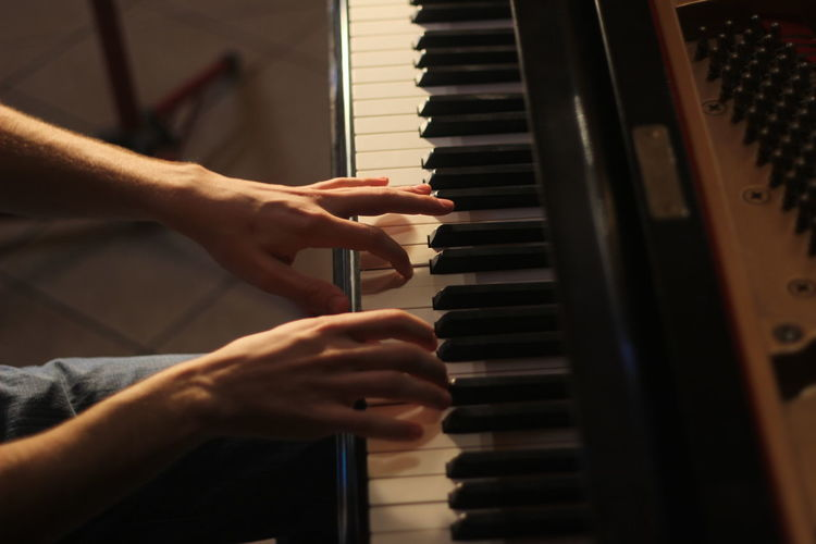 Cropped Image Of Man Playing Grand Piano During Sunset