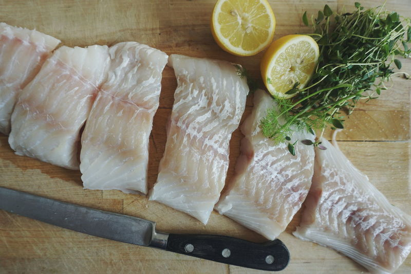 fresh cod fillet on a woodboard together with fresh thyme and lemon Fish Raw Raw Fish COD Cod Fish Top View Top Perspective Food Healthy Eating Cutting Board Preparation  SLICE Kitchen Knife Preparing Food Ingredient High Angle View Raw Food Lemon Close-up Chopping Board Knife Raw Healthy Food Healthy Nutrition Halved Thyme