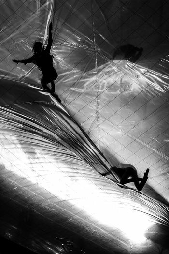 High angle view of silhouette people walking on ceiling