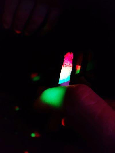 Close-up of hand against illuminated light